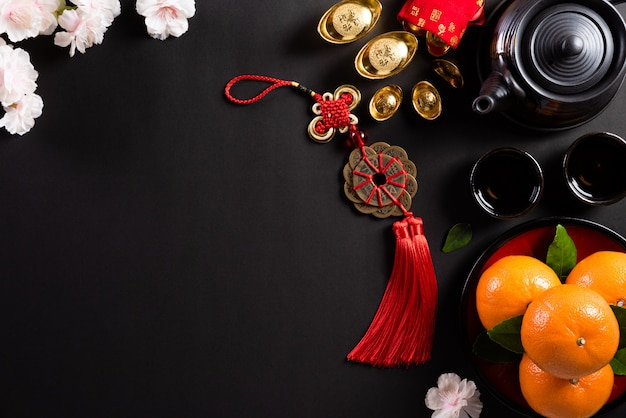 Chiński nowy rok ozdoby festiwalowe pow lub czerwony pakiet, sztabki pomarańczy i złota lub złota bryła na czarnym tle.