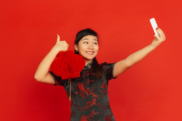 Chiński nowy rok. portret młodej dziewczyny azji na białym tle na czerwonym tle. modelka w tradycyjnych strojach wygląda na szczęśliwą i robi selfie z dekoracją. uroczystość, święto, emocje.