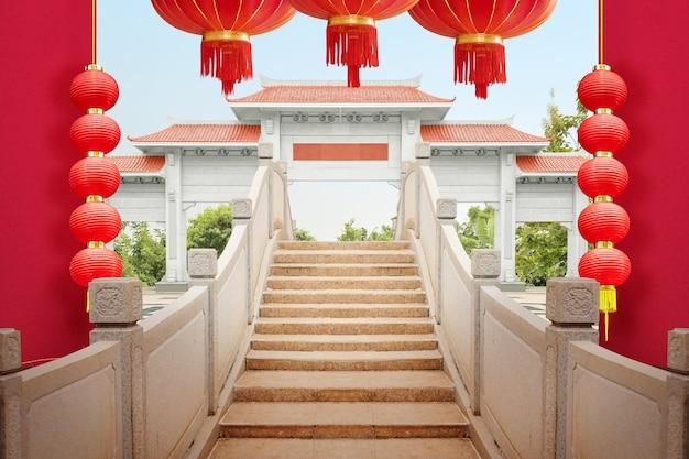 Chiński pawilon brama z czerwonym dachem i most łukowy z wiszącą czerwoną latarnią