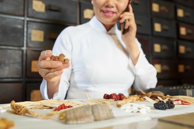 Chiński pracownik apteki gospodarstwa suchego grzyba shiitake
