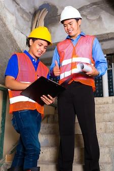 Chiński przełożony lub kontroler i pracownik lub architekt patrzą na plac budowy w schowku