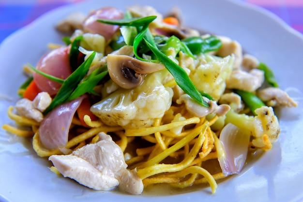 Chiński smażony makaron z kurczakiem, warzywami i zieloną cebulą. chrupiący makaron w sosie z kalafiorem, pieczarkami, filetem, zbliżenie