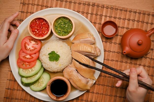 Chiński styl żywności. ryż po hajnańskim kurczaku podawany z bulionem, przepis na azjatyckie jedzenie. ręka i pałeczki