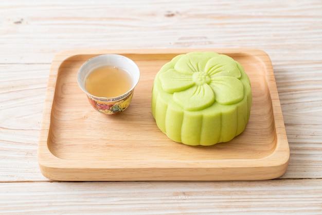 Chiński tort księżycowy o smaku zielonej herbaty z herbatą na drewnianym talerzu