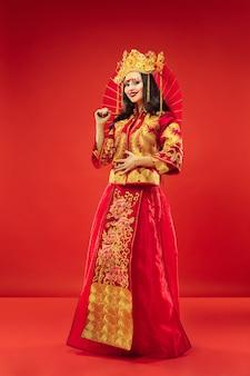 Chiński tradycyjny pełen wdzięku kobieta w studio na czerwonym tle. piękna dziewczyna w stroju ludowym. chiński nowy rok, elegancja, wdzięk, wykonawca, wydajność, taniec, aktorka, koncepcja ubioru