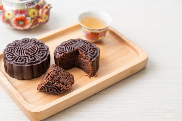 Chińskie ciasto księżycowe o smaku ciemnej czekolady na drewnianym talerzu