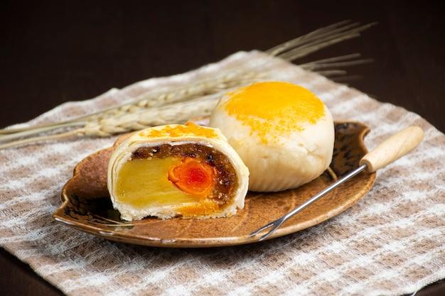 Chińskie ciasto księżycowe z solonym jajkiem w talerzu w kształcie liścia na drewnianym stole
