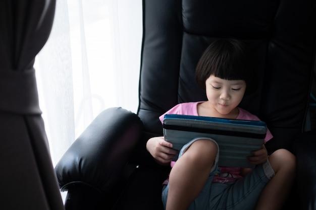 Chińskie dziecko uzależnione od telefonu, azjatycka dziewczyna gra w smartfona, dziecko korzysta z telefonu, ogląda kreskówkę