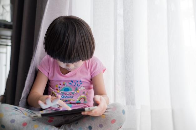 Chińskie dziecko uzależnione od telefonu, azjatycka dziewczyna gra w smartfona, dziecko używa telefonu, ogląda kreskówkę