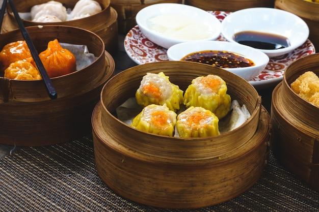 Chińskie gotowane na parze i smażone bułeczki w drewnianych parowcach