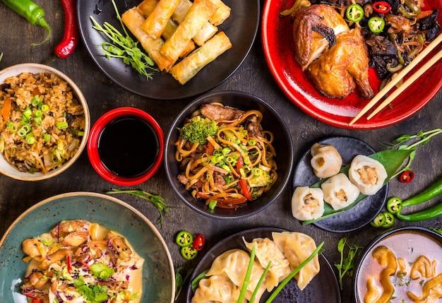 Chińskie jedzenie ciemne tło. makaron chiński, ryż, pierogi, kaczka po pekińsku, dim sum, sajgonki