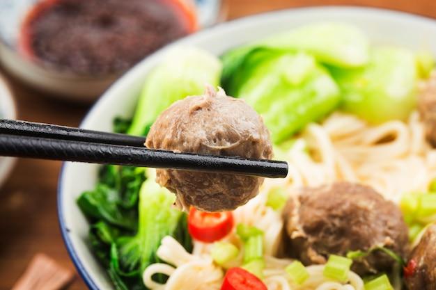Chińskie jedzenie: klopsiki podawane z makaronem,