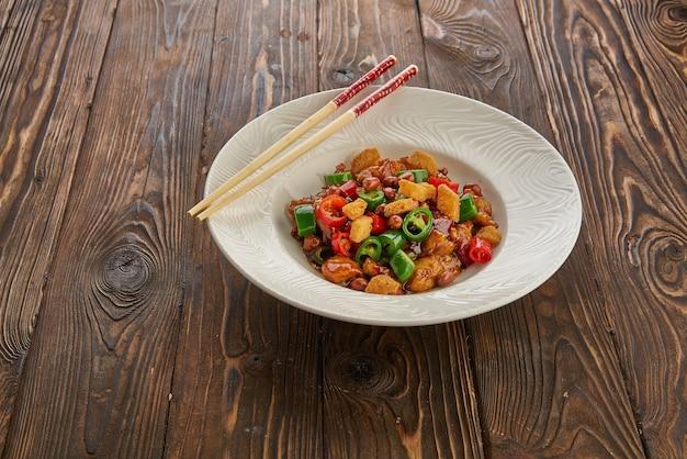 Chińskie jedzenie, kurczak kung pao w białej płytce z pałeczkami na drewnianym stole, widok z góry i miejsce na kopię