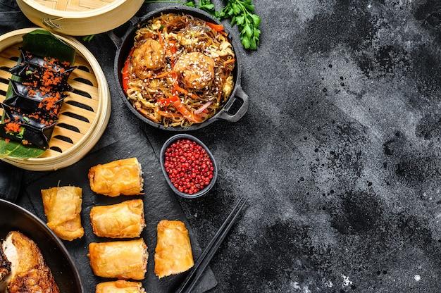Chińskie jedzenie. makaron, pierogi, smażony kurczak, dim sum, sajgonki. zestaw kuchni chińskiej. czarne tło