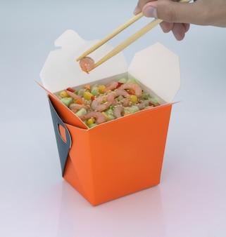 Chińskie jedzenie na wynos krewetki z warzywami w kartonowym pudełku na jasnym tle