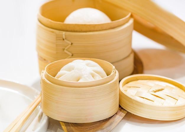 Chińskie knedle bułeczki gotowane na parze, bułka gotowana na parze podawane w drewnianym koszu