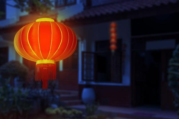Chińskie lampiony wiszące przed domem na tle sceny nocnej