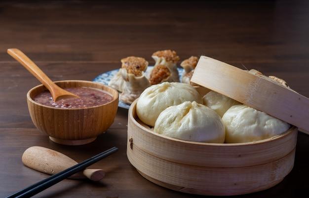 Chińskie śniadanie. na stole są bułeczki na parze i owsianka
