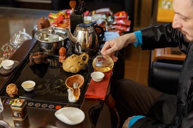 Chińskie tradycje. mistrz nalewa herbatę ze szklanego czajniczka.