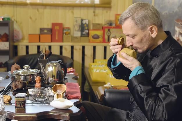 Chińskie tradycje. mistrz wdycha aromat herbaty podczas ceremonii parzenia herbaty.