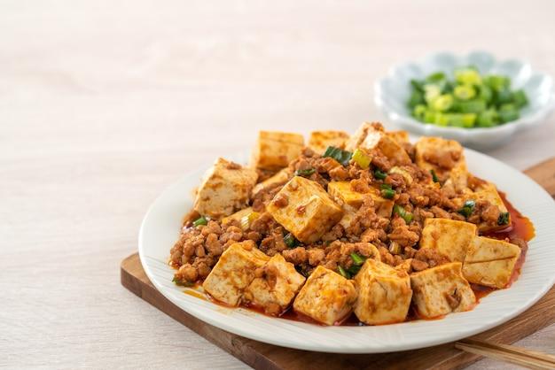 Chińskie Tradycyjne Smażone Tofu Z Ostrym Sosem Na Drewnianym Stole Premium Zdjęcia