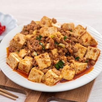 Chińskie tradycyjne smażone tofu z ostrym sosem na drewnianym stole