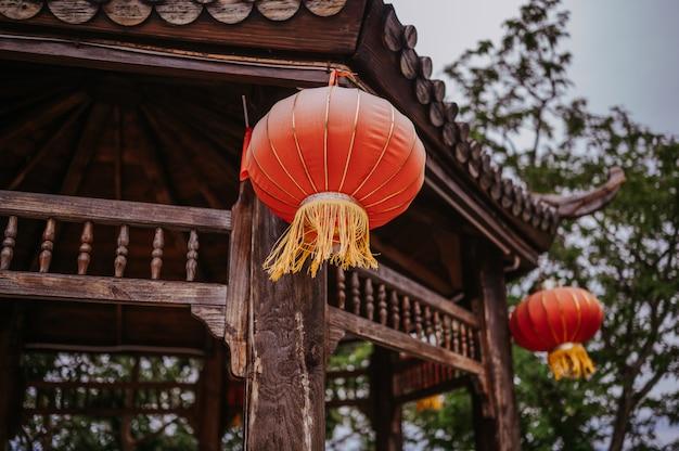 Chiny podróżują chińskimi czerwonymi latarniami wiszącymi na drewnianej pagodzie lub altanie w parku przyrody na banner z okazji chińskiego nowego roku księżycowego
