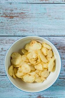 Chips ziemniaczany w białej misce i na misce na kolor drewna niebieski kolor grunge