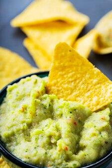 Chipsy guacamole i nachos na ciemnym tle. sos guacamole z chipsami kukurydzianymi na łupkowej desce. zbliżenie. selektywne skupienie