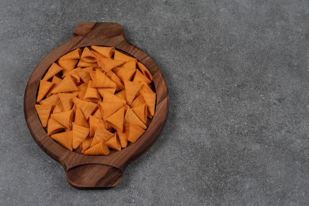 Chipsy kukurydziane i suszony chleb na drewnianej tacy na marmurowej powierzchni