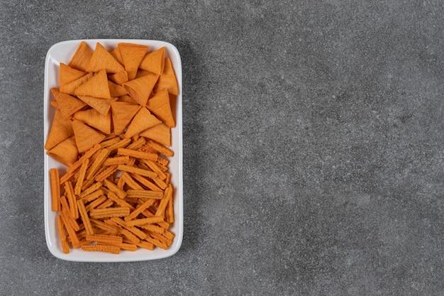 Chipsy kukurydziane i suszony chleb w misce na marmurowej powierzchni