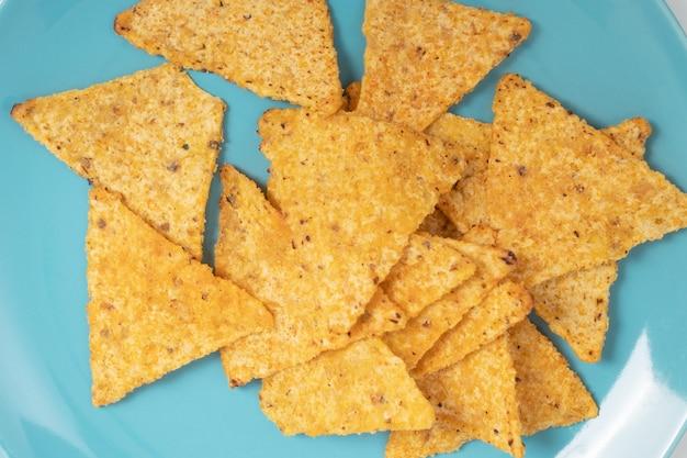 Chipsy kukurydziane nachos na niebieskim talerzu