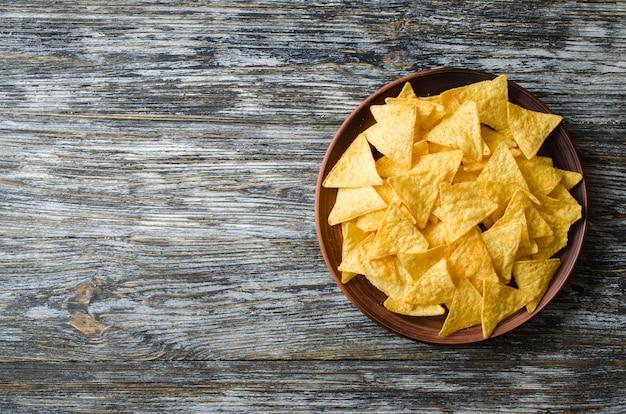 Chipsy kukurydziane nachos w talerzu na drewnianym stole. meksykańskie jedzenie koncepcja.