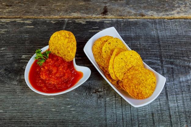 Chipsy kukurydziane nachos z pikantnym sosem adjika na stole