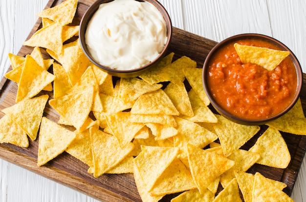 Chipsy kukurydziane nachos z pikantnymi pomidorami i sosami serowymi.