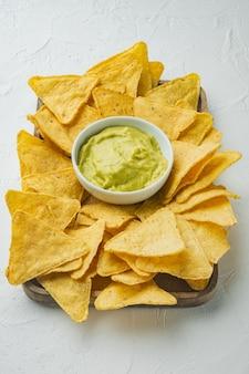 Chipsy kukurydziane nachos z tradycyjnym sosem dip, na białym stole