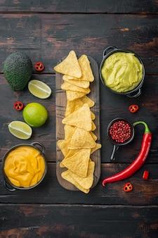 Chipsy kukurydziane nachos z tradycyjnym sosem dipowym, na starym drewnianym stole, widok z góry lub leżak na płasko