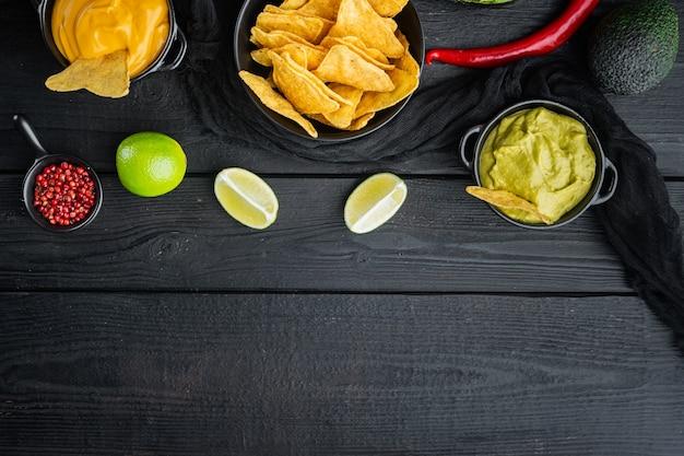 Chipsy kukurydziane nachos z tradycyjnym zestawem sosów dipowych, na czarnym drewnianym stole, widok z góry lub leżak na płasko