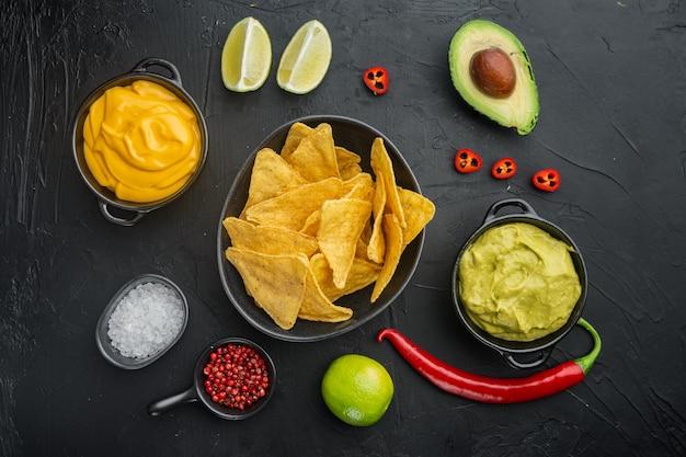 Chipsy kukurydziane nachos z tradycyjnym zestawem sosów dipowych, na czarnym stole, widok z góry lub na płasko