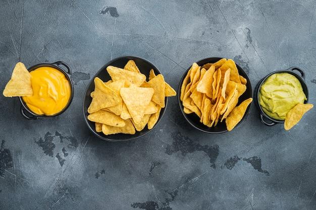 Chipsy kukurydziane nachos z tradycyjnym zestawem sosów dipowych, na szarym stole, widok z góry lub na płasko