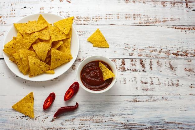 Chipsy kukurydziane nachos ze świeżą domową salsą na jasnym drewnianym stole