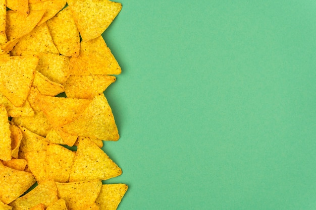 Chipsy kukurydziane tortilla są rozrzucone na kolorowym tle z miejscem na tekst