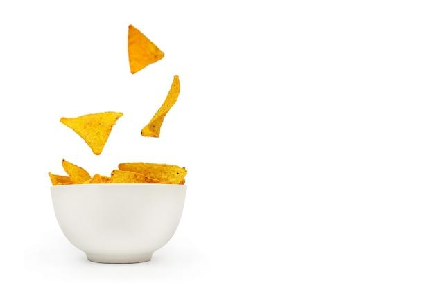 Chipsy kukurydziane tortilli wpadają do białej ceramicznej miski na białym tle z miejscem na tekst