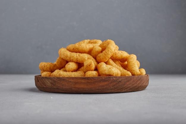 Chipsy kukurydziane w przyprawach na drewnianym talerzu.