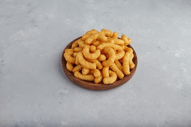 Chipsy kukurydziane w przyprawach w drewnianym talerzu, widok z góry.