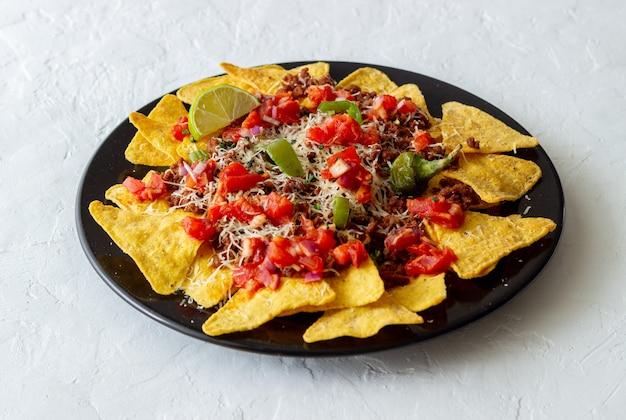 Chipsy kukurydziane z mięsem, serem, pomidorami i papryką. meksykańskie jedzenie. kuchnia narodowa.