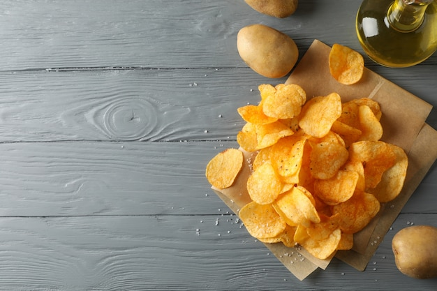 Chipsy na papierze rzemieślniczym, sault, oliv oliv, ziemniaki na szarym drewnie, miejsce na tekst. widok z góry
