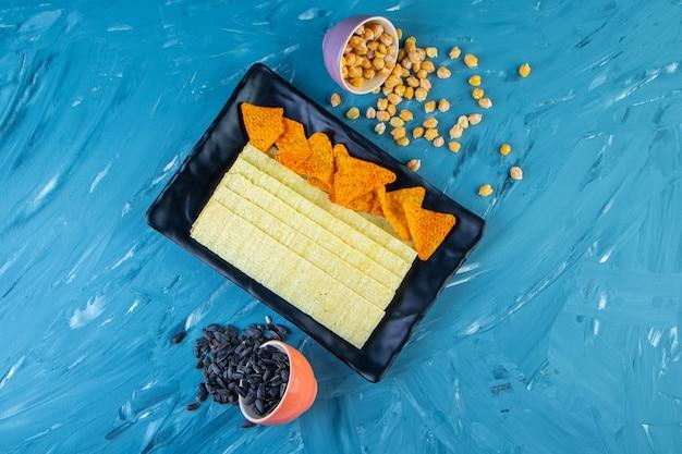 Chipsy nachos i chipsy długie na półmisku obok nasion i ciecierzycy, na niebieskiej powierzchni.