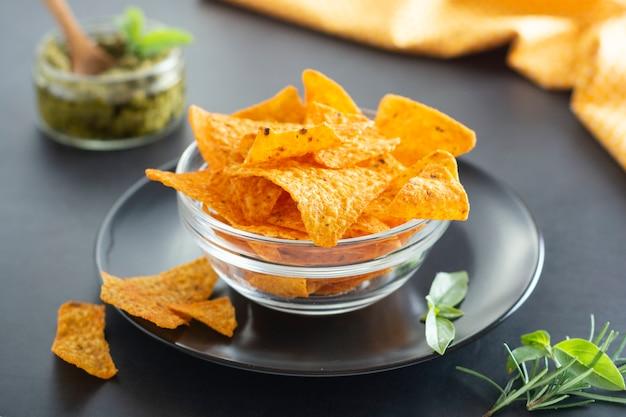 Chipsy nachos lub meksykańskie chipsy kukurydziane w szklanej misce, na białym tle zdrowe przekąski