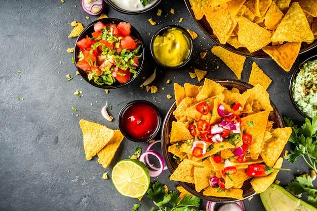 Chipsy nachos z różnymi dipami, tradycyjna meksykańska przekąska na talerzu